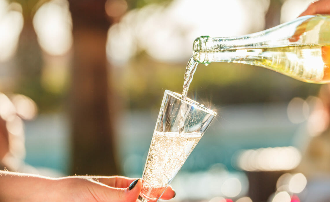Pouring Prosecco sparkling wine into a glass, on a summer day