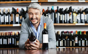 Wine shop keeper comparing two bottles of Barolo wine of different quality and price