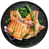 Grilled pork chops on a plate with green chives and herbs