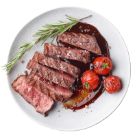 Sliced beef Steak on a plate with rosemary herb and fried tomatoes