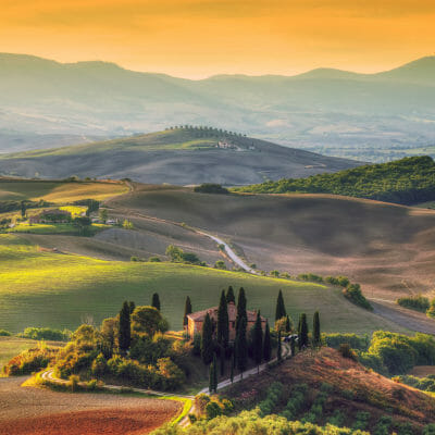 Sunrise over farm house and vineyard in Tuscany