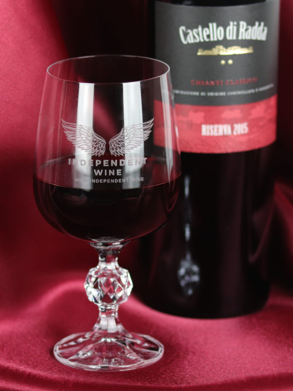Independent Wine official crystal goblet on red silk background, with a bottle of Chianti Classico Riserva red wine