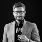 Oleg Dmitriev, Wine Portfolio Director of Independent Wine, holding a glass of red wine