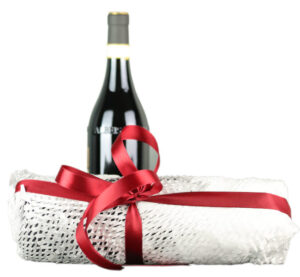 Bottle of wine wrapped as a gift, and a bottle of red wine behind