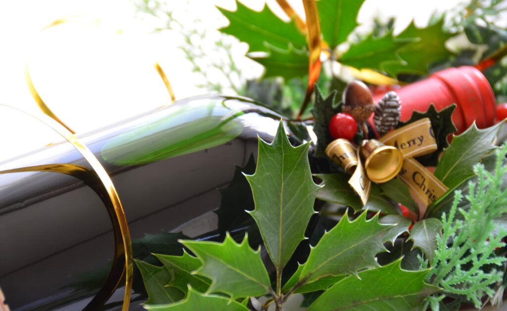 Christmas Wine Gift and Holly leaves and berries and Christmas decoration