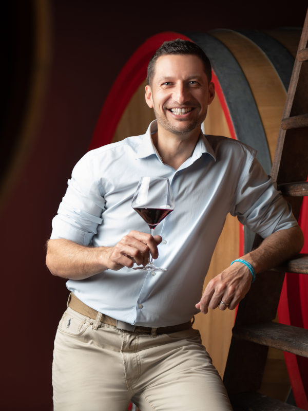Winemaker Paolo Demarie holding a glass of Barolo wine in his cellar in Barolo DOCG