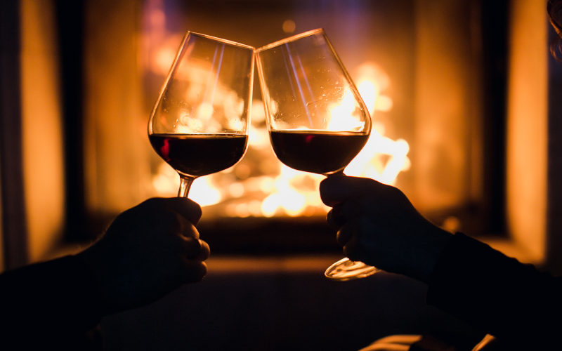 Couple with glasses of red wine toasting in front of fireplace