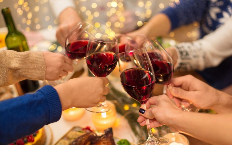 Friends celebrating Christmas and toasting with red wine