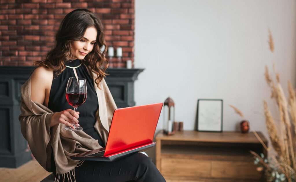 Woman in elegant dress with laptop and glass of wine doing virtual wine tasting