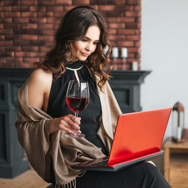 Woman with glass of wine and laptop tasting wine