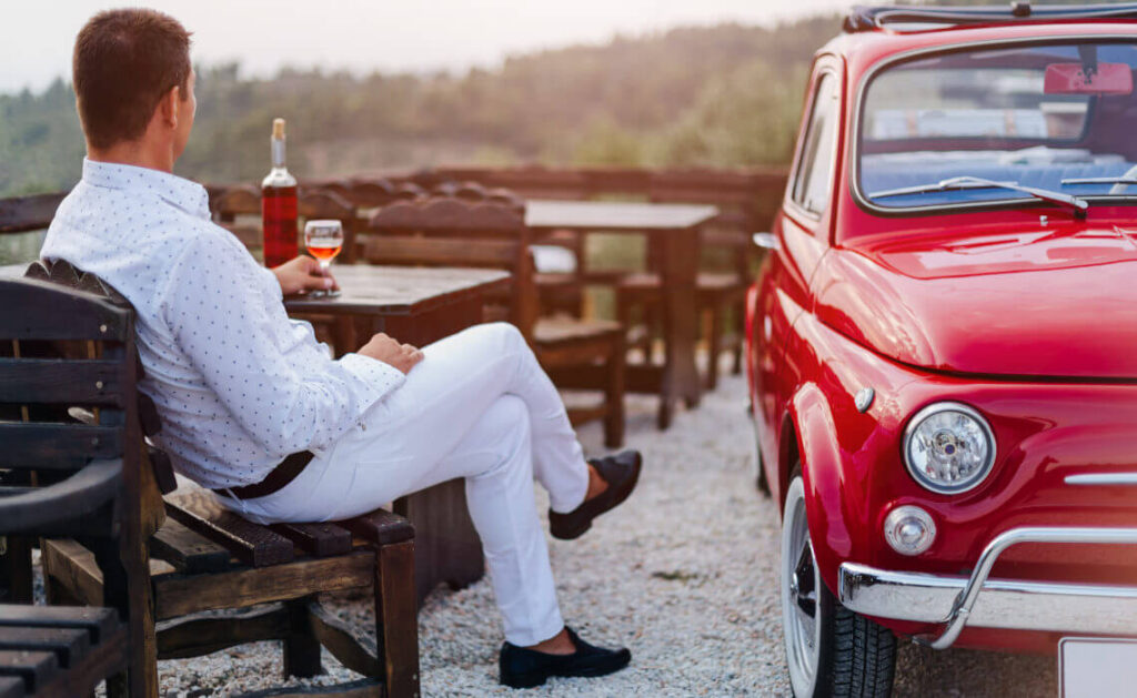 Italian chap drinking wine near his red car