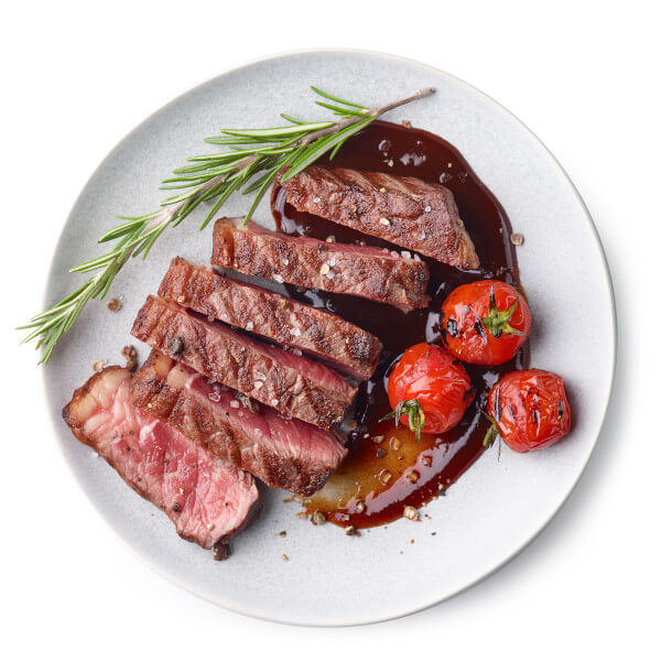 Sliced Grilled Beef Steak on a plate with rosemary herb and fried tomatoes