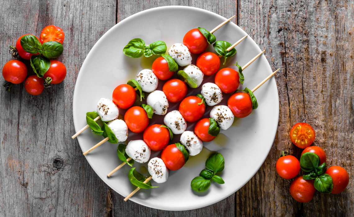 Plate with Italian starters caprese stewers Mozzarella cheese cherry tomatoes and basil leaves on sticks