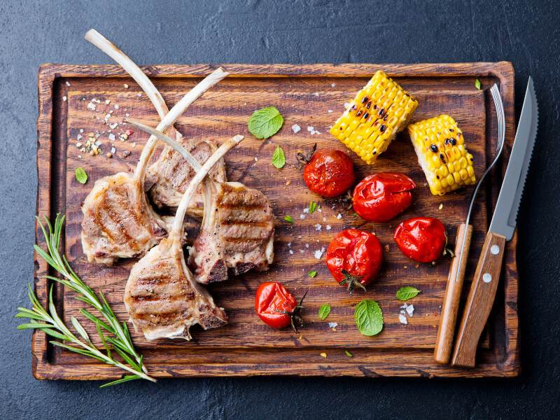Flame grilled lamb ribs on a wooden board with roasted tomatoes, corn and rosemary herb
