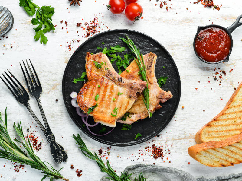 Grilled pork chops on a plate with green chives, herbs, barbecue sauce and slices of bread