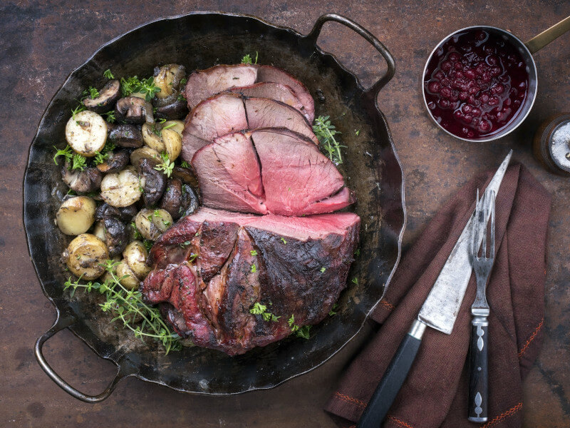 Roasted venison with mushrooms and potatoes and cranberry sauce